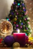 Kerze, alte Uhr und Weihnachtsbälle mit Winterdekoration Stockbild