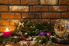 Kerze, alte Uhr und Weihnachtsbälle mit Winterdekoration Lizenzfreie Stockbilder