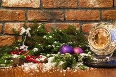 Kerze, alte Uhr und Weihnachtsbälle mit Winterdekoration Lizenzfreies Stockfoto