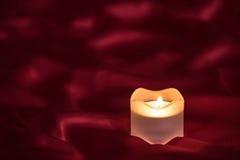 Kerze auf dem roten Stoff stockfotografie