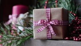 Kerze auf dem Tisch nahe dem Weihnachtsbaum Geschenk und Stechpalme stockfotos