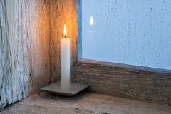 Kerze auf der Schwelle eines Fensters Lizenzfreie Stockbilder