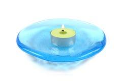 Kerze auf einem blauen Glasteller stockfoto