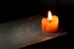 Kerze auf einem Buch, dunkle Nacht Lizenzfreie Stockfotos