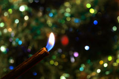 Kerze auf einem Hintergrund von Lichtern Stockbild