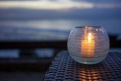 Kerze auf einer Tabelle mit Strandansicht bei Sonnenuntergang lizenzfreies stockfoto