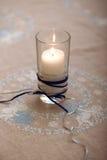Kerze auf gestickter Tischdecke Stockfotografie