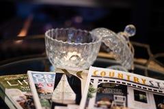Kerze auf Glastisch mit Zeitschriften ausgebreitet stockfotografie