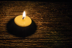 Kerze auf hölzernem schwarzem Hintergrund Stockbilder