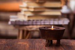 Kerze auf Holztisch mit Büchern im Hintergrund Lizenzfreie Stockfotografie