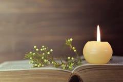 Kerze, Buch und Blumen stockbild