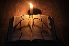 Kerze, Buch und Gläser Stockfoto