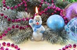 Kerze in der Form des Schneemannes mit Nadelbaum und Flitter Lizenzfreies Stockbild