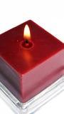 Kerze, die auf Weiß brennt Stockbild