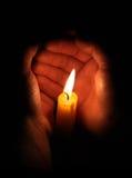 Kerze, die in den Händen brennt Stockbild