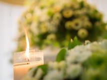 Kerze, die mit Blumen-Hintergrund brennt Stockfoto