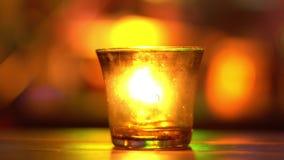 Kerze in einem Glasaufenthalt auf Holztisch in der Blaumusikstange Unscharfes Backround Bokeh Farbige Beleuchtung 4K stock footage