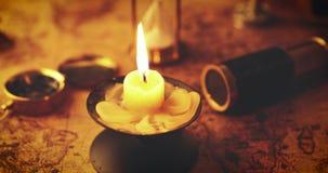 Kerze im Kerzenständer auf der Karte der Alten Welt mit anderen Retro- Einzelteilen stock video footage
