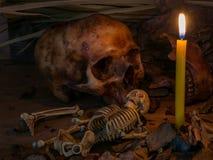 Kerze mit dem Schädel und Apfel auf hölzernem Tabellenhintergrund, Stillleben Lizenzfreie Stockfotos