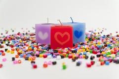 Kerze mit drei Farben auf kleinem buntem Plastikgefäß Lizenzfreies Stockbild