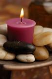Kerze mit Steinen Stockbild