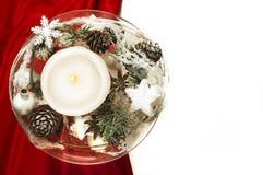Kerze mit Winterdekoration auf roter Seide und weißem Hintergrund Lizenzfreies Stockbild
