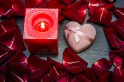 Kerze, rotes Blumenblatt stieg mit Geschenkbox auf Tabelle Rote Rose und Inneres über Weiß Lizenzfreie Stockfotografie