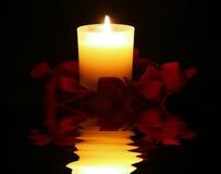 Kerze umgeben durch rosafarbene Blumenblätter mit Reflexion stockfotos