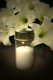 Kerze und Blumen für Beileid stockbild