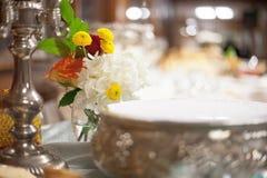 Kerze und Blumen an versorgtem Hochzeitsempfang Lizenzfreie Stockbilder