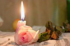 Kerze und Rose, die auf dem Musik shee liegen lizenzfreies stockfoto