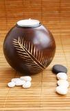 Kerze und Steine auf Bambusmatte Lizenzfreie Stockfotografie
