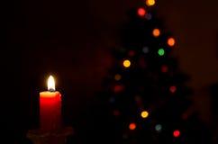 Kerze und Weihnachtslichter Stockfotografie