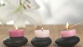Kerzen angehoben auf die Kiesel, die beleuchtet werden stock video