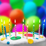 Kerzen auf einem Geburtstagskuchen auf dem Hintergrund von Ballonen Stockfotos
