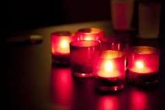 Kerzen in den roten Glasleuchtern. Lizenzfreie Stockbilder