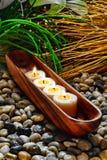 Kerzen, die im hölzernen Behälter in einem holistischen Badekurort brennen Stockfotos