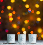 Kerzen, die im Schnee mit defocussed feenhaftem Lichter, Orange oder Goldenem bokeh im Hintergrund stehen Lizenzfreies Stockfoto