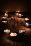 Kerzen, die nachts auf einem hölzernen Hintergrund 2 brennen Stockfotos