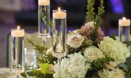 Kerzen, die in Stemware und in Rosen für Hochzeitsempfang schwimmen Stockbilder