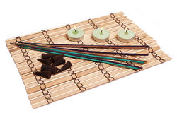 Kerzen, Duftkegel und Steuerknüppel auf Bambusmatte stockfotografie