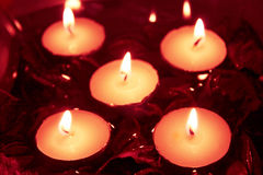 5 Kerzen in einer Schüssel mit Wasser und roten trockenen Blumen Stockfotos