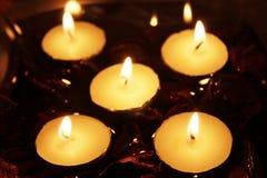 5 Kerzen in einer Schüssel mit Wasser und trockenen Blumen Stockbilder