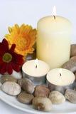 Kerzen mit Kieseln und Blumen Stockbild