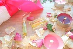 Kerzen mit wesentlichem Badekurortöl brennend, stieg Blumenblumenblätter und weißes Tuch auf Holztischhintergrund lizenzfreie stockfotos