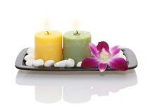 Kerzen, Orchidee und Kiesel in der schwarzen Platte Stockbild
