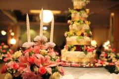 Kerzen und Blumenblumensträuße nähern sich Hochzeitstorte Stockbild