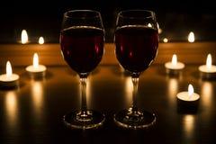 Kerzen und ein Glas Wein steuern Abend automatisch an Stockbild