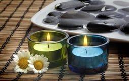 Kerzen und Gänseblümchen vor schwarzen Kieseln Stockbild