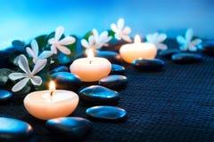 Kerzen und schwarze Steine auf schwarzer Matte Lizenzfreies Stockbild